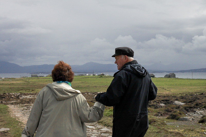 The King of Tory Island, Patsy Dan Rogers escorts Thin Places Tours guest on a walk across Tory Island