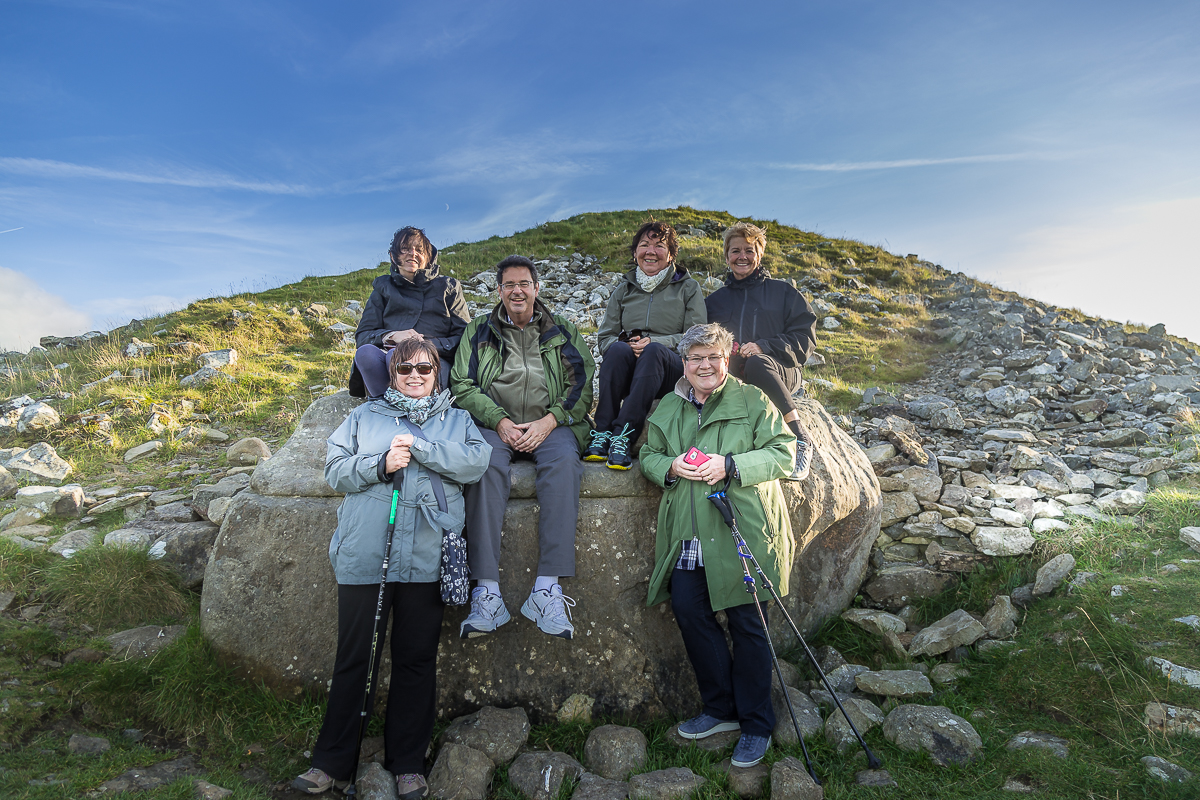 "Guests seated in the ""hag's chair"" at Loughcrew - Hill of the Hag"